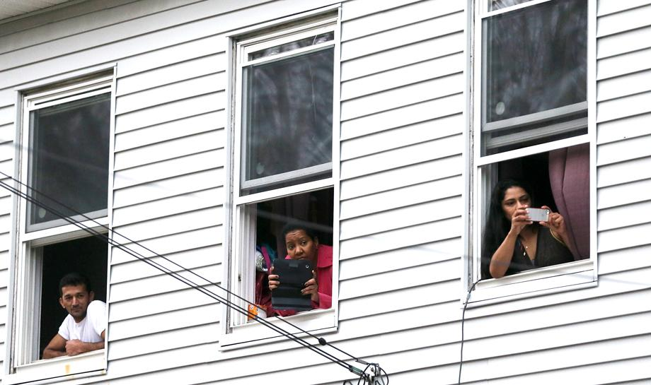 Onlookers take pictures as they watch from windows while SWAT team members search for one remaining suspect at a neighboring apartment building on April 19, 2013 in Watertown, Massachusetts.