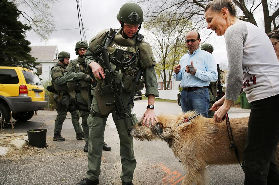 A SWAT team member pets a dog as they conduct a door-to-door search for 19-year-old Boston Marathon bombing suspect Dzhokhar A. Tsarnaev on April 19, 2013 in Watertown, Massachusetts.