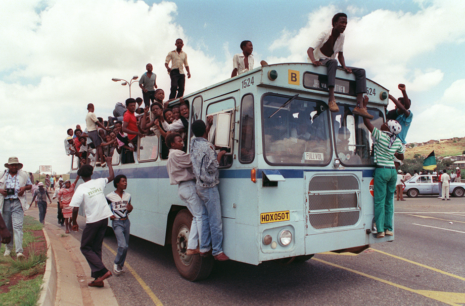 Jubilant inhabitants of Soweto find room where they can in and on a bus to reach Orlando stadium in Soweto, 12 February 1990, to attend a mass African National Congress (ANC) rally to be addressed by freed anti-apartheid leader and African National Congress (ANC) member Nelson Mandela. It's the first rally Nelson Mandela is holding since his release from jail, 11 February 1990.