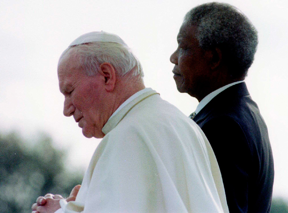 South African President Nelson Mandela (R) and Pope John Paul II listen to national anthems after they met at Johannesburg International Airport September 16, 1995, at the start of the pope's first official visit to the country.
