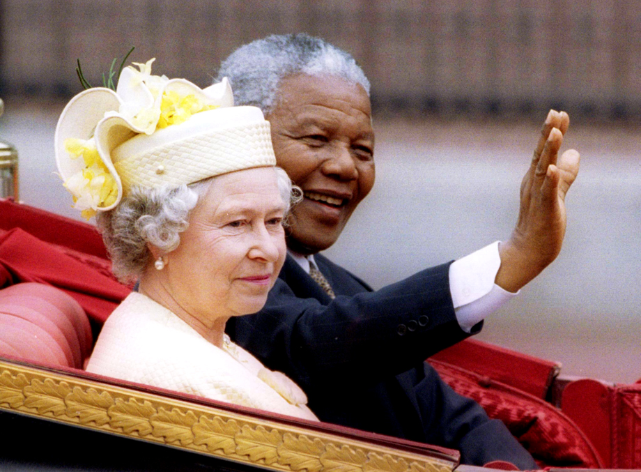 Nelson Mandela and Britain's Queen Elizabeth II ride in a carriage outside Buckingham Palace on the first day of a state visit to Britain, July 9, 1996.