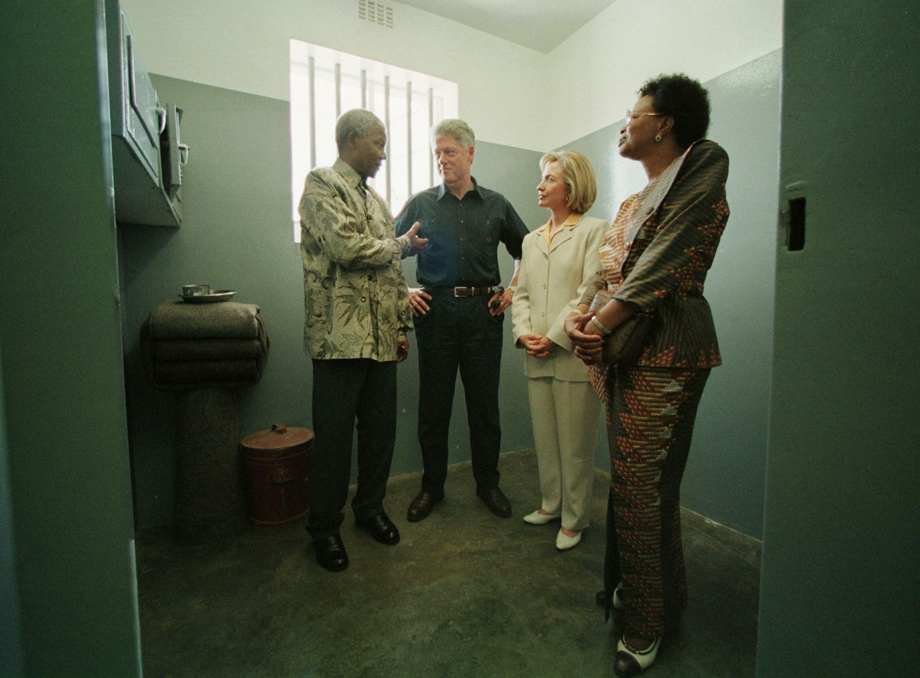 "South African President Nelson Mandela talks to Bill and Hillary Clinton March 27 from inside his former prison cell on Robben Island where he spent 18 years. Clinton said he was glad Mandela survived the experience without ""having his heart turned into stone."" At right is Mandela's partner Graca Machel."