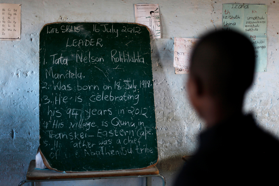 School children read the history of former South African President Nelson Mandela written on a chalkboard, ahead of the opening of a container library by the Bill Clinton foundation in celebration of Mandela day, at a school in Qunu, July 17, 2012.