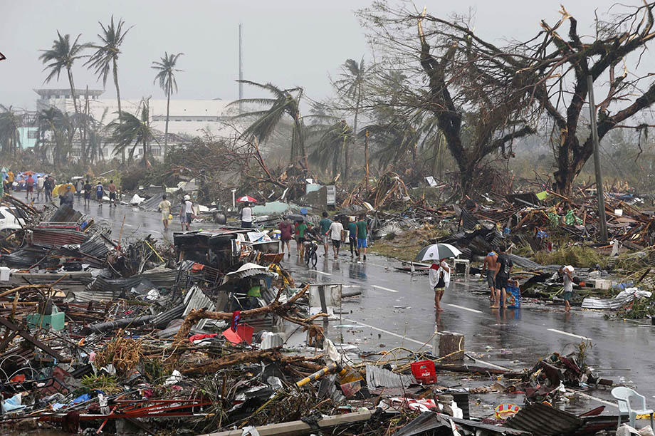 Residents walk on a road littered with debris after Super Typhoon Haiyan battered Tacloban city in central Philippines November 10, 2013.