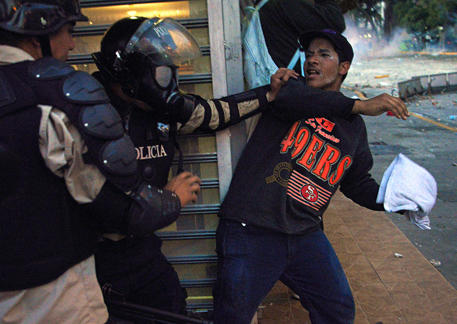 A member of the National Police struggles with an anti-government student taking part in a protest, in Caracas.