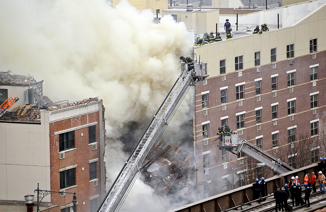 Firefighters from the Fire Department of New York respond to the five-alarm fire and building collapse.