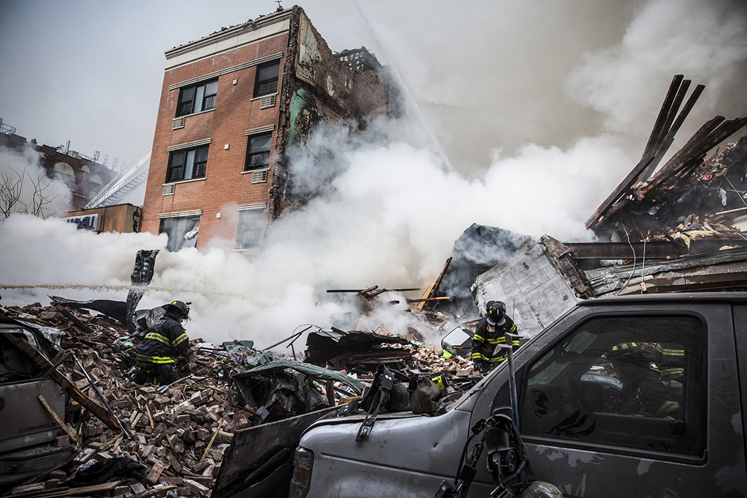 Heavy smoke pours from the debris at the site of a building collapse at Park Avenue and East 116th Street.