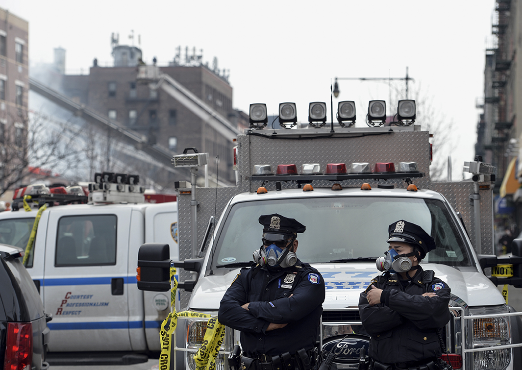 New York City Police Department officers wear masks at the scene of the explosion.
