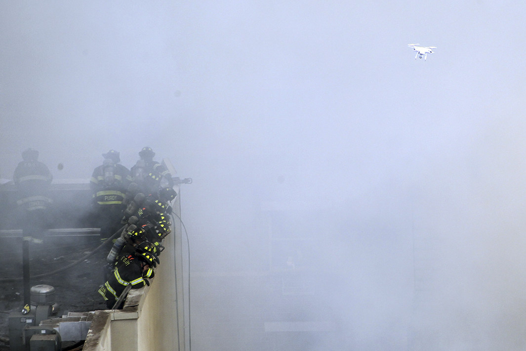 Firefighters respond to the building collapse as a drone flies overheard.