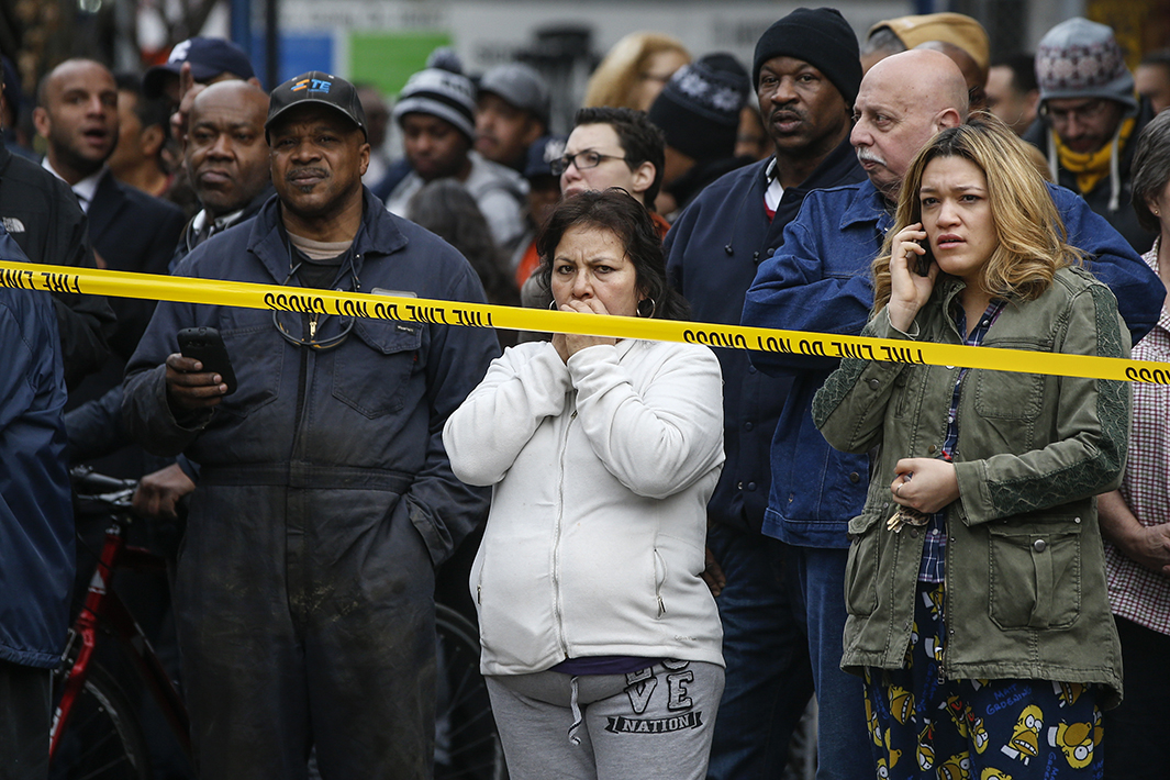 Residents watch as the Fire Department of New York searches for anyone trapped in the debris.