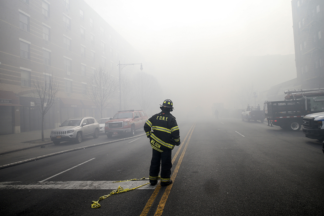 A firefighter stands on smoke-filled East 116th Street.
