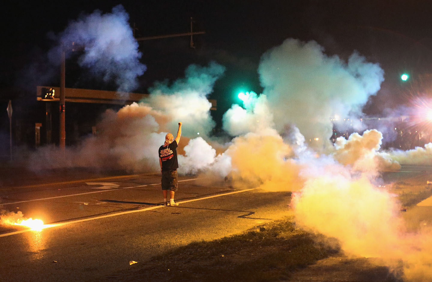 A demonstrator, protesting the death of teenager Michael Brown, stands his ground as police fire tear gas on August 13, 2014 in Ferguson, Missouri.