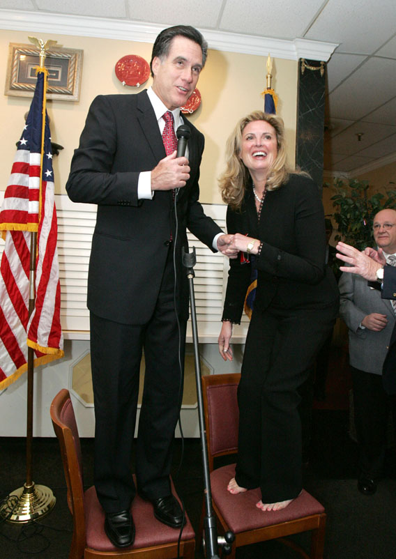Mitt Romney, left, helps his wife Ann onto a chair so they can be seen by the crowd gathered as he campaigns at Thursdays Too restaurant in Rock Hill, South Carolina