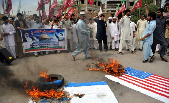 Pakistani Shiite Muslims shout slogans beside a burning Israeli flag during a rally against Israel and the United States.