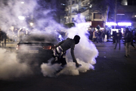 Egyptian protester throwing tear gas.
