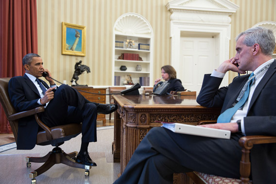 President Obama (L) talks on the phone and Chief of Staff Denis McDonough.