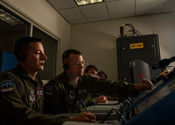 U.S. Air Force Capt. Daniel Moore, front, and Capt. Kyle Heiderich, back, check a launch control center.