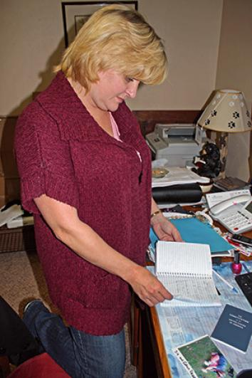 Kathy Smith reviews notes on her son's case in her home