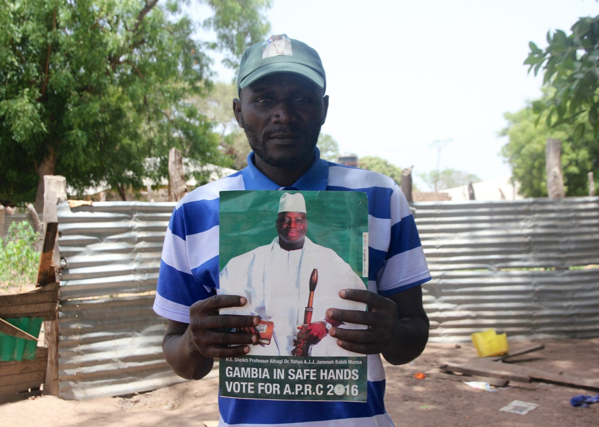 Kujabi poses with a sign from Jammeh's losing 2016 campaign he left me as a gift.