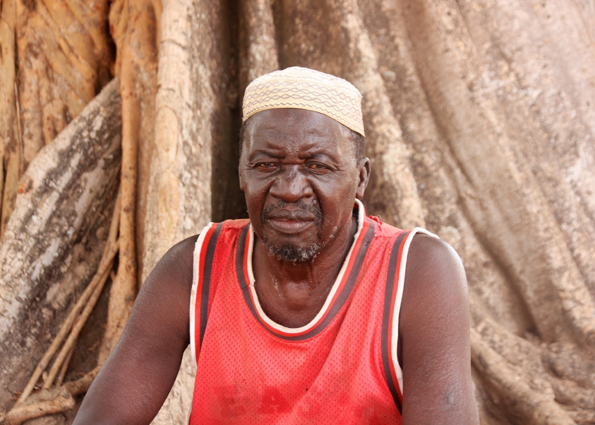 Kanilai village chief, Bakary Jammeh, sits under a silk cotton tree. He is Yahya Jammeh's cousin.