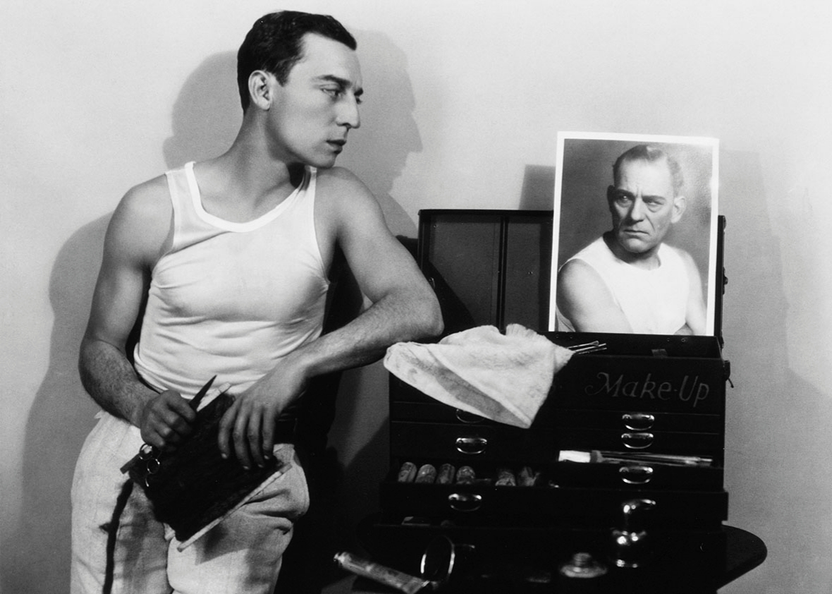 A gelatin silver print showing the silent comedian Buster Keaton looking at a photo of Lon Chaney.