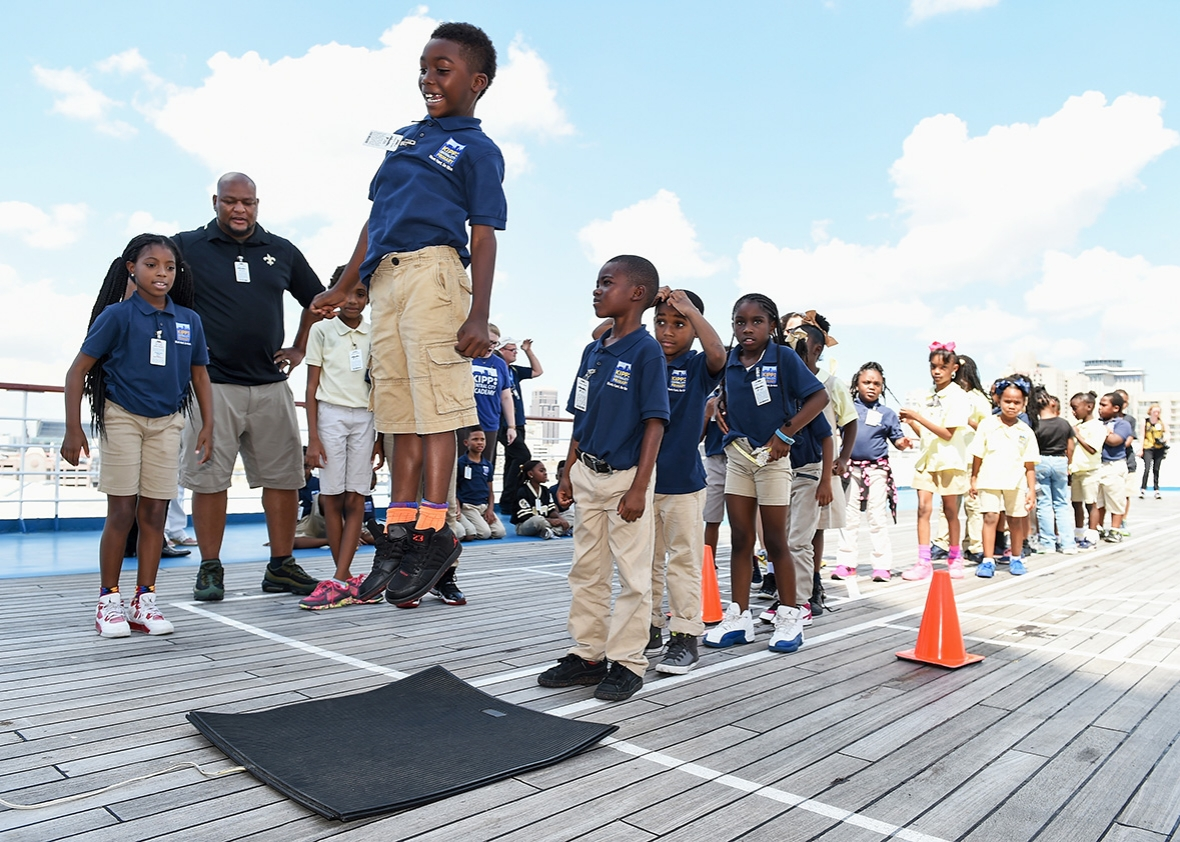 At an event to promote literacy on board the Carnival Triumph while it is docked at the Port of New Orleans, former New Orleans Saints running back Deuce McAllister works with students from Kipp Central City Primary School on September 8, 2016 in New Orleans, Louisiana.