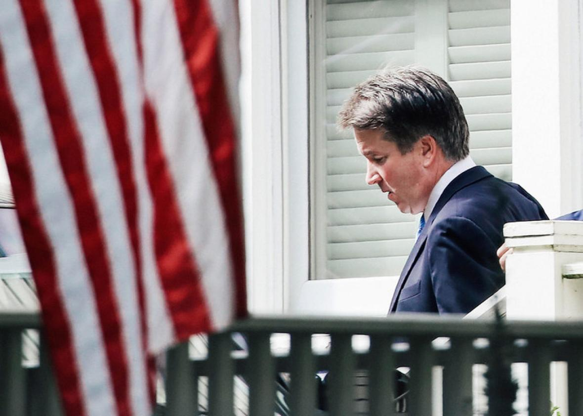 Brett Kavanaugh, eyes downcast, walking out of his home, with an American flag in the foreground.