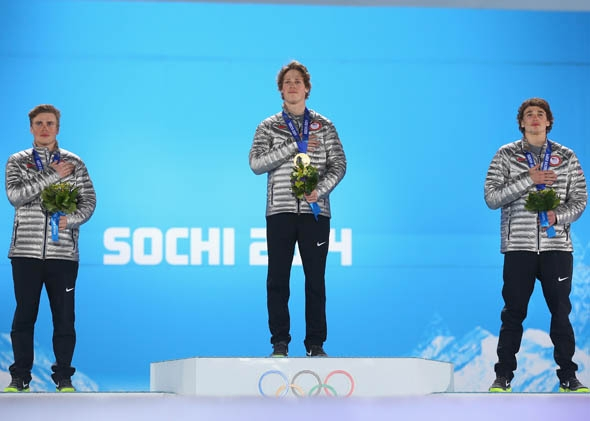 Silver medalist Gus Kenworthy of the United States, gold medalist Joss Christensen of the United States and bronze medalist Nicholas Goepper of the United States pose during the National Anthem during the medal ceremony for the Freestyle Skiing Men's Ski Slopestyle on day six of the Sochi 2014 Winter Olympics.