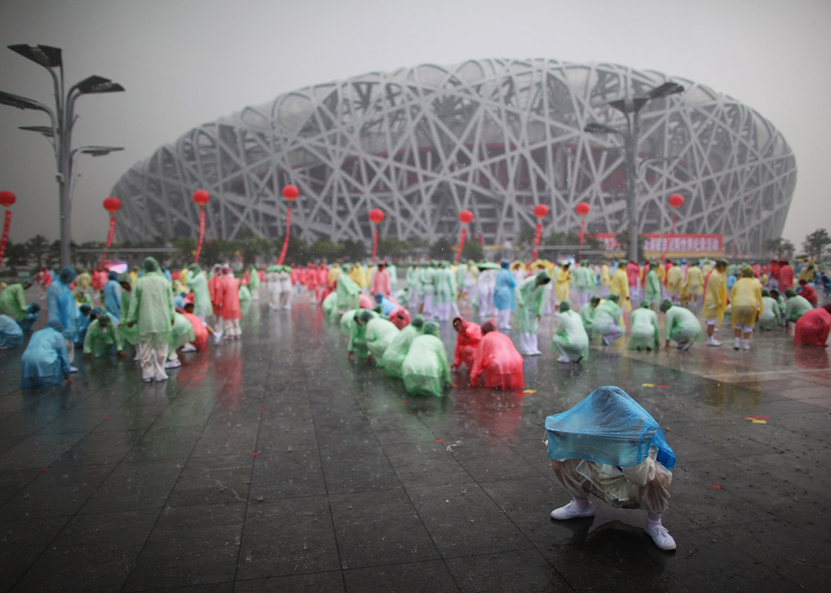 People prepare to perform tai chi in the rain outside the 2008 Olympic stadium, known as the Bird's Nest, on Aug. 8, 2009, in Beijing.