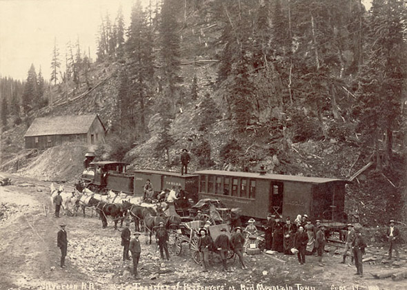 Buggies, wagons, and horse teams by a Silverton Railroad passenger car in Red Mountain Town, Ouray County, Colorado, 1888.