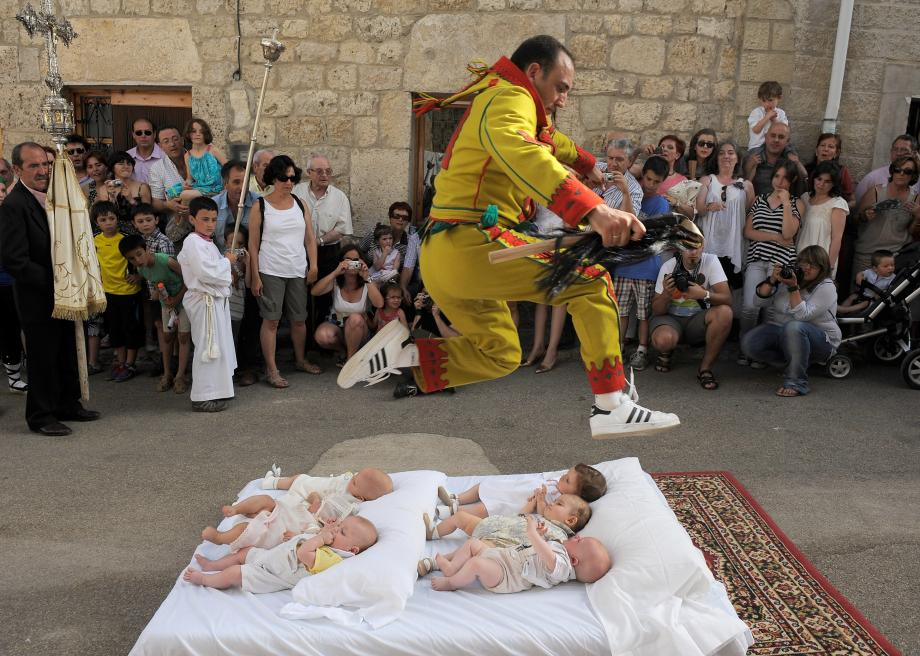 117374793-man-representing-the-devil-leaps-over-babies-during-the