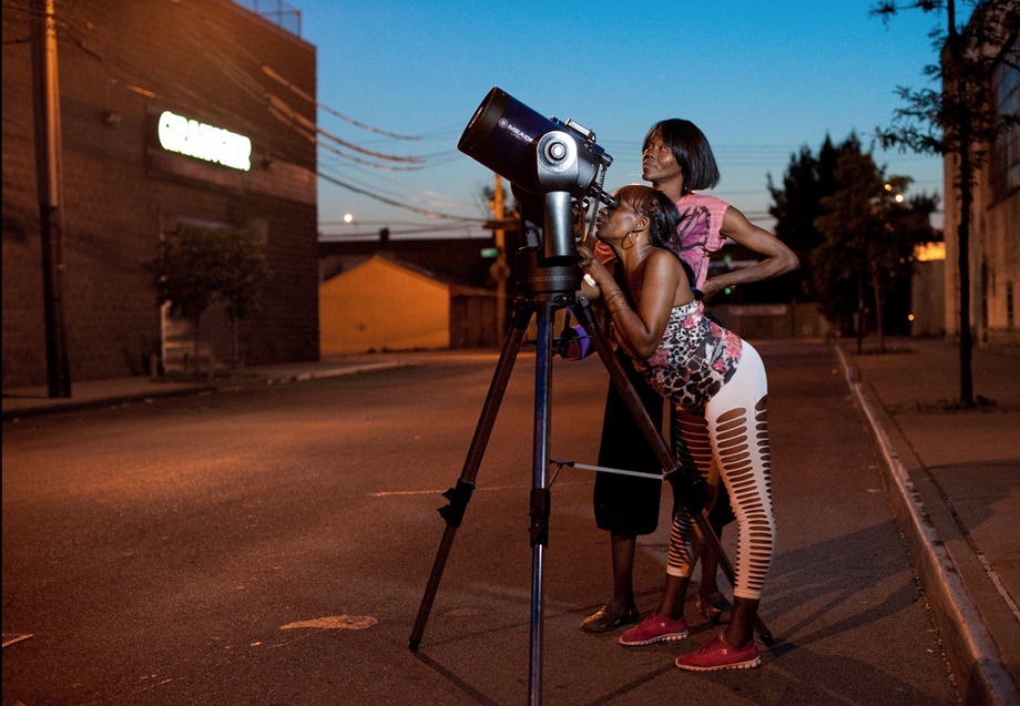 two women looking into a telescope