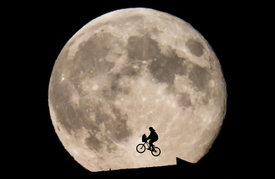 biker silhouetted in front of the Moon