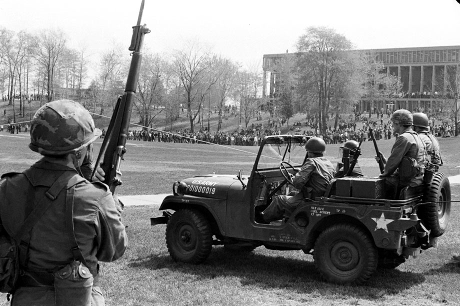 Guardsmen watch from a distance as students gather in the Commons late in the morning of May 4, 1970.