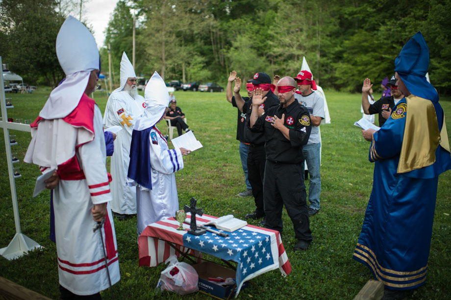 "Canidates wishing to become initiated into the Ku Klos Knights of the Ku Klux Klan take their oaths as part of a the naturalization ritual.Naturalization is becoming a citizen of the Invisible Empire, and not unlike becoming a Naturalized citizen of the United States"", according to a comment made by the late Imperial Wizard Dale Fox. ""There are some parts of the ceremony that many might at first mistake for a ""hazing"". Proposed Klansmen are blindfolded, and then with one arm placed on the shoulder of the man before him, led through the woods at a sometimes-vigorous pace. The link is not to be broken as they are questioned and intimidated occasionally with the sound of a firearm.This ""hazing"" actually has symbolic purpose, and builds mutual trust, loyalty and reveals personal bravery and dedication. Candidates are brought before the Klan for acceptance into the Invisible Empire and are quizzed on their Klan craft and Klan history. They are instructed in the history of the six eras of the Klan. They participate in swearing certain oaths and at the conclusion they are ""Knighted"" as in the days of old, by anointing with sacred waters and a sword touch on both shoulders followed by a benediction. Finally, the new citizens of the Invisible Empire are greeted and welcomed by the officiating officers. Tennessee."