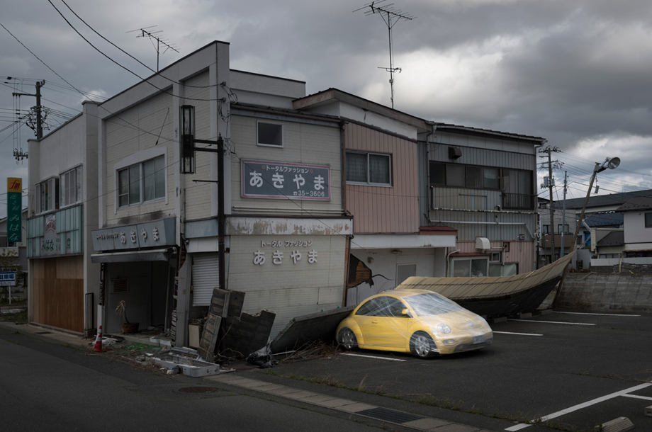 The town of Namie. All objects in the forbidden zone, including the car, cannot be taken back by their owners for reasons of contamination. The vehicles are abandoned in the parking awaiting for destruction.