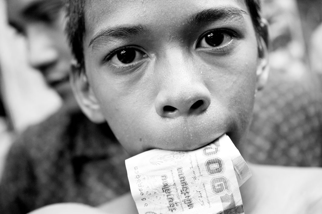 A boy with money in his mouth. After winning the boxing match winner goes around and collects money from tourists certificates. After that, the money is divided, the coach gets the largest share.