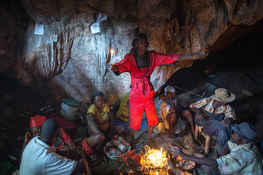 A Vodou priest (Hougan or Houngan) begins to invoke the spirits (Loa or Iwa) during the feast day of St. Francis De Assisi in a remote region of Haiti.