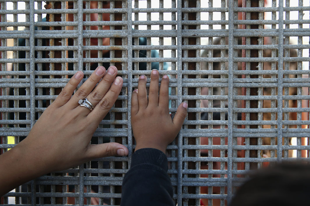 San Diego, Calif. Family members reunite through bars and mesh of the U.S.-Mexico border fence at Friendship Park on November 17, 2013 in San Diego, Calif. The U.S. Border Patrol allows people on the American side to visit with friends and family through the fence on weekends, although under supervision from Border Patrol agents. Access to the fence from the Tijuana, Mexico side is 24/7. Deportation and the separation of families is a major theme in the immigration reform debate.