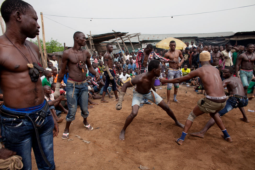 "Lagos, Nigeria- A match between two fighters is stopped by another boxer in Lagos, Nigeria. Each match consists of three rounds. The match is stopped if a boxer's ""spear"" becomes unraveled or if one boxer hits the ground."