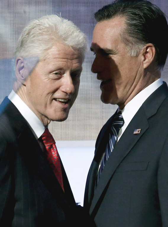 Former U.S. President Bill Clinton stands with Republican presidential candidate Mitt Romney.