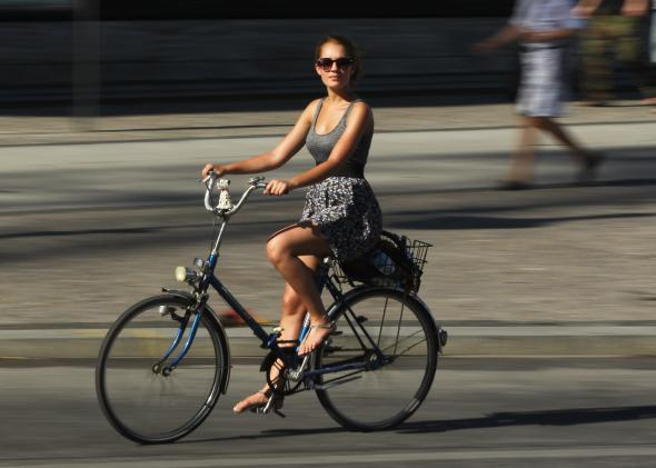 117638917-young-woman-rides-a-bicycle-on-a-hot-day-in-the-city
