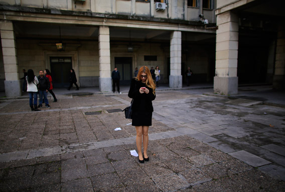 A woman holds a cell phone as she stands next to a courthouse in the Andalusian capital of Seville February 20, 2013.