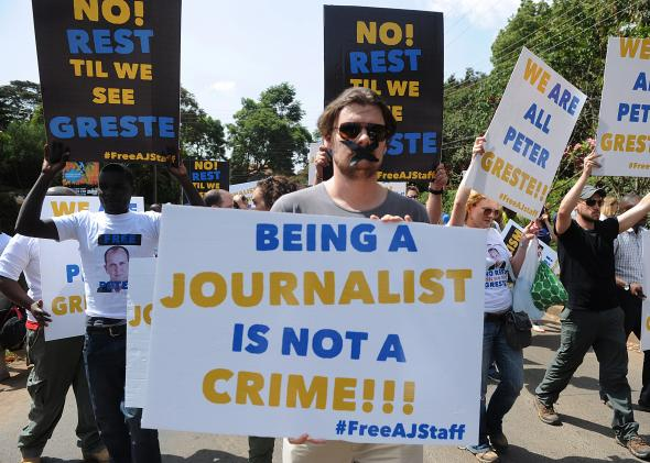 466799149-foreign-journalists-hold-banners-as-they-march-to-the