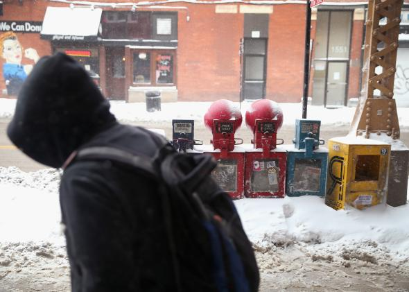 466944731-pedestrian-navigates-a-snow-covered-sidewalk-during-his_1