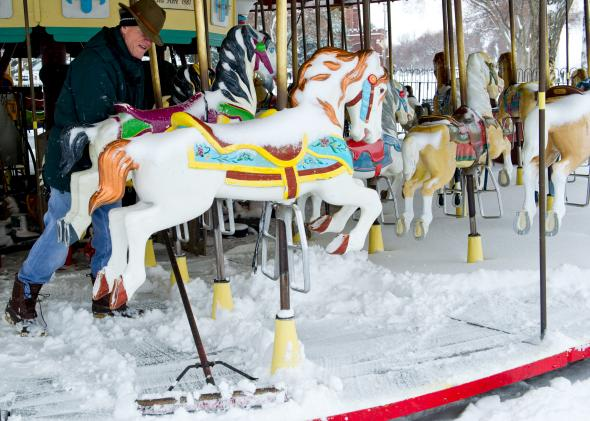 479272501-worker-clears-snow-from-the-carousel-on-the-national