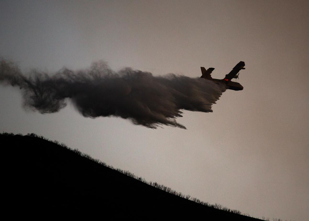 A firefighting aircraft drops water on Aug. 16, 2015 in the Angeles National Forest north of Castaic, California.