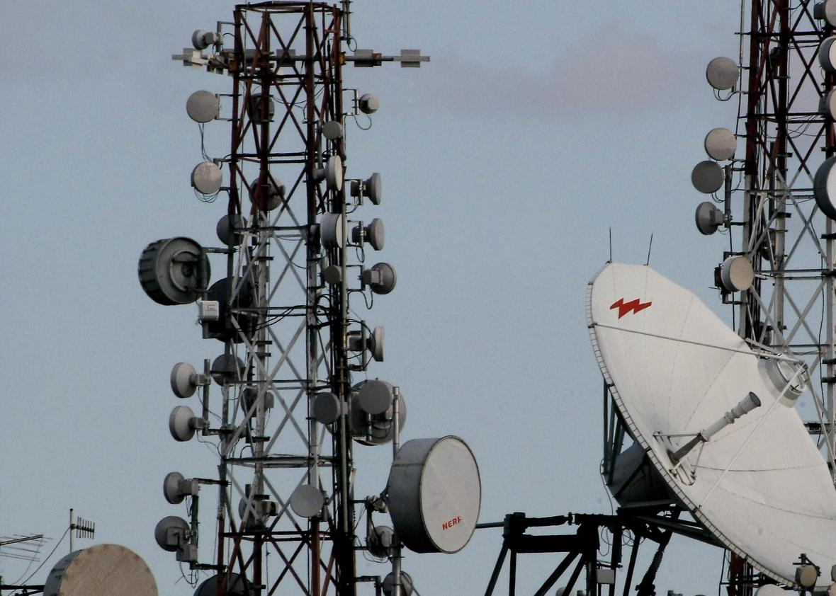 85522063-satellite-dishes-and-cell-phone-towers-atop-a-roof-of-a