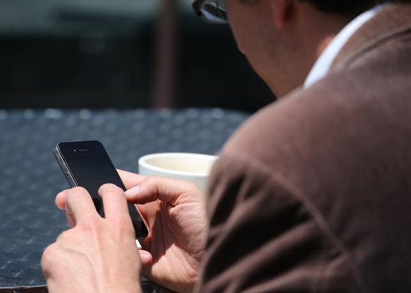 169973293-man-uses-a-smartphone-as-he-sits-in-union-square-on