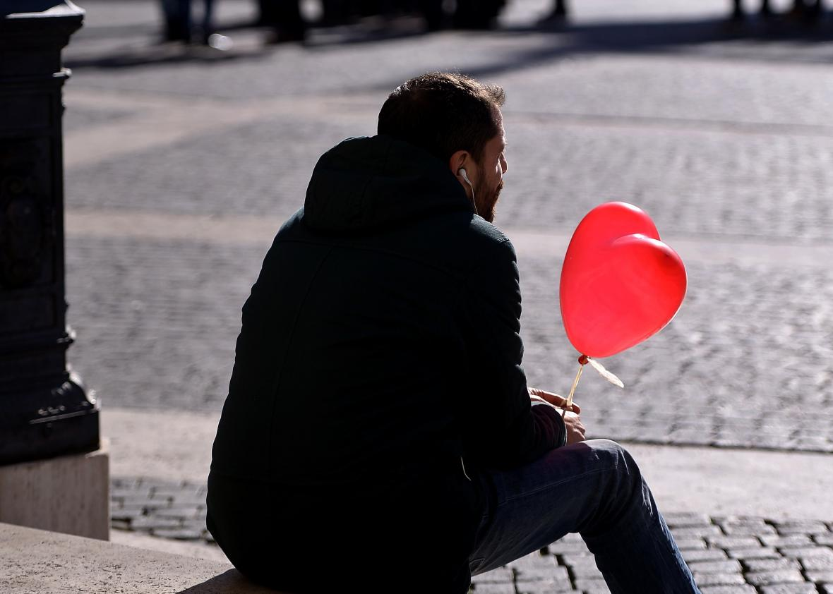 462404212-man-holding-a-heart-shaped-balloon-waits-in-romes